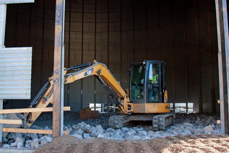 Mini excavator demolishing grain bin floor at FWS site.