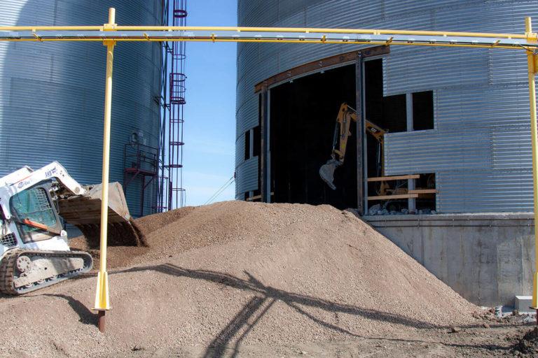 Mini excavator and bobcat removing concrete at FWS site.