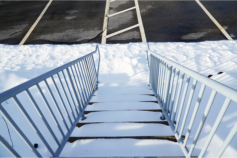 Snow covered stairs are safety hazards that need to be identified.