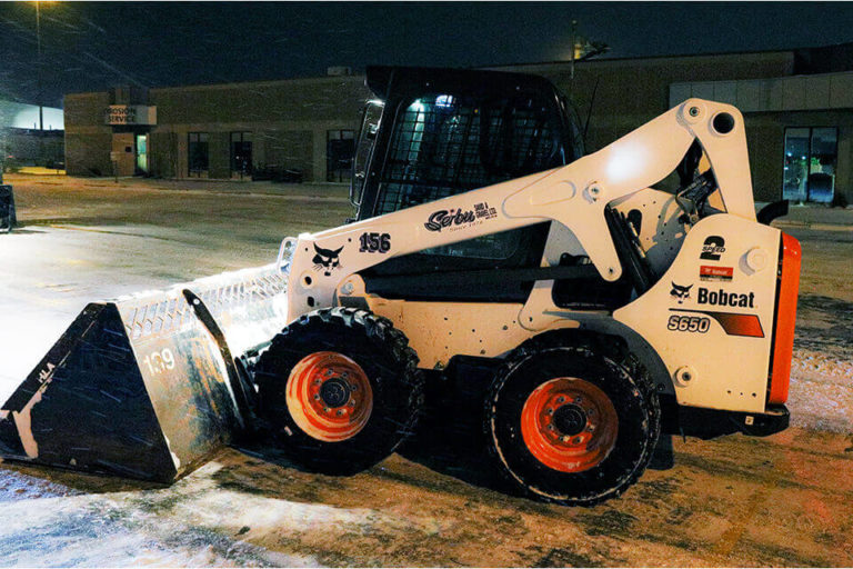 Serbu's bobcat clearing snow from commercial property.