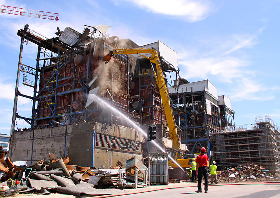 Spraying water at demolition site helps control dust.