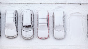 Parked cars covered in snow.