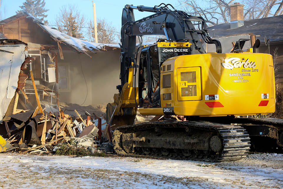 Excavator demolishing a residential house in Regina.