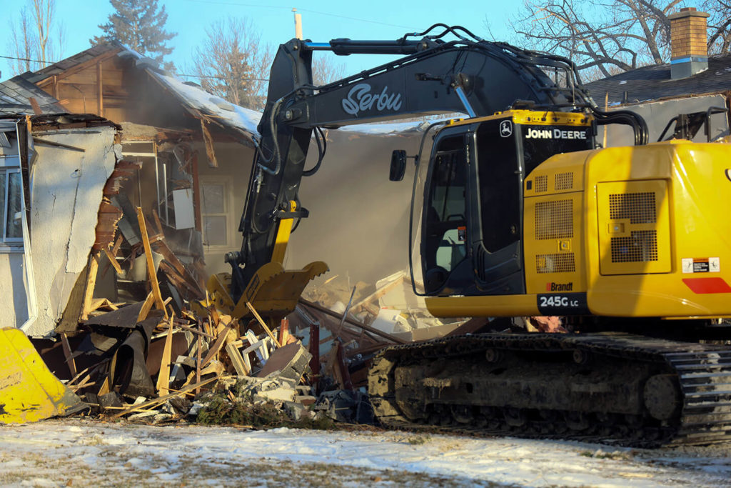 Excavator demolishing a residential building in Regina.