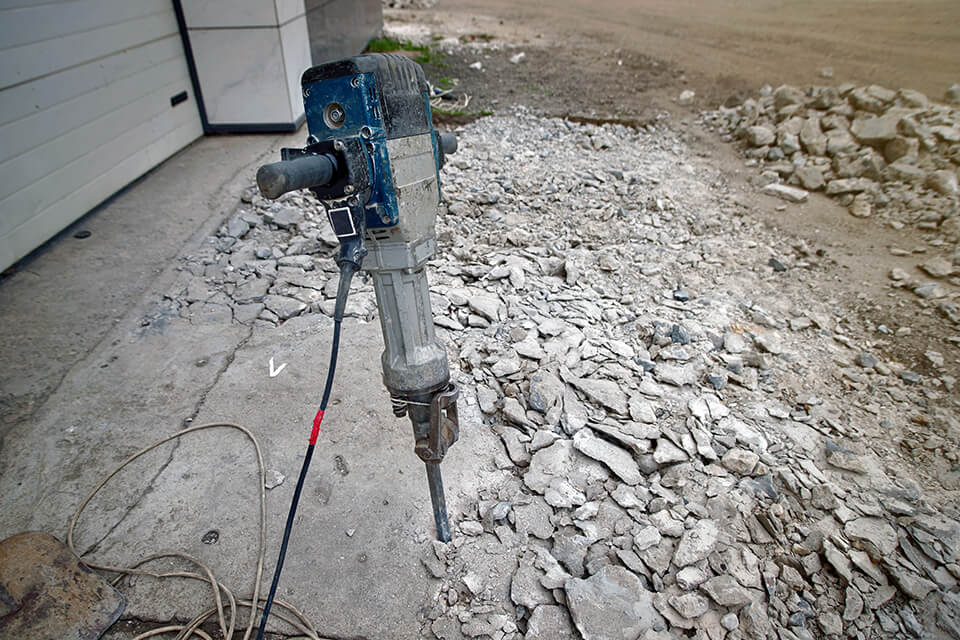 A jackhammer being used to break up a concrete driveway.