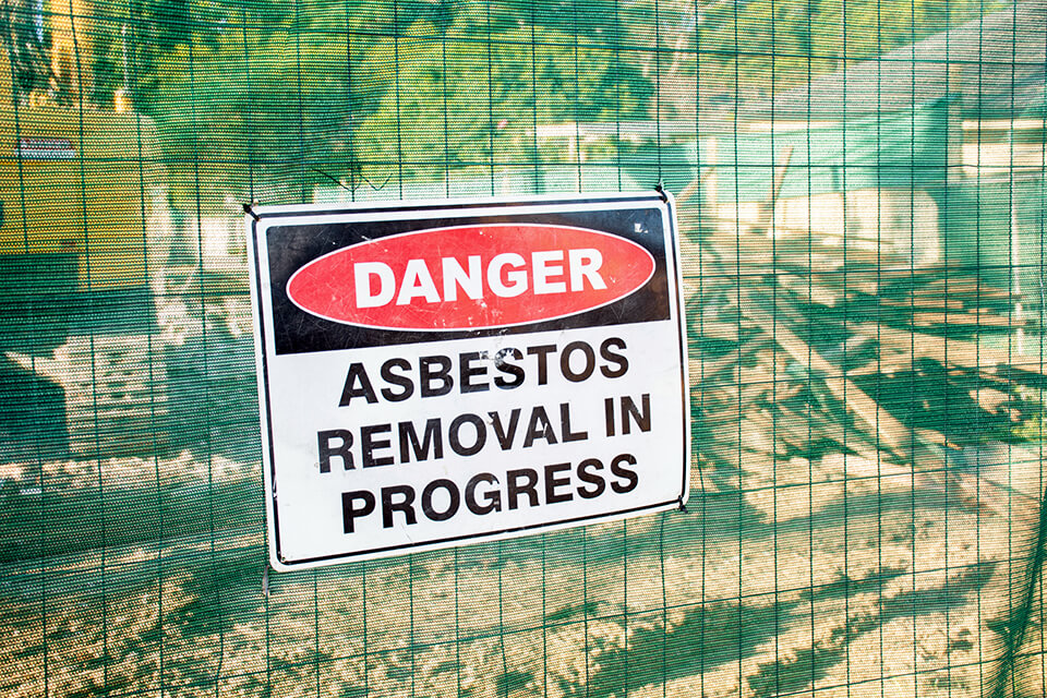 Asbestos in progress sign displayed during demolition.