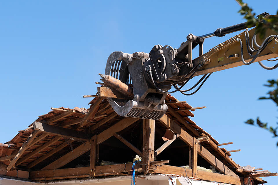 An excavator demolishing the roof of a house.